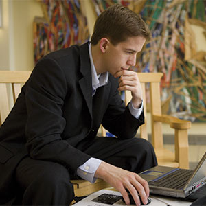 A man in a suit looks at a laptop