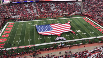 Large flag on the field at a Huskers football game